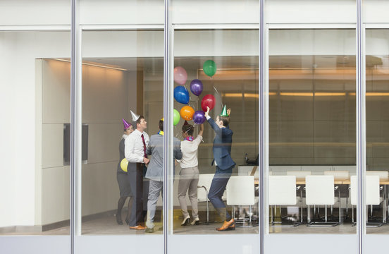 Playful business people in party hats celebrating balloons in conference room