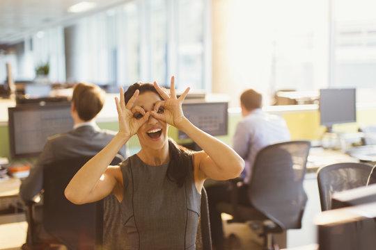 Portrait of playful businesswoman pretending to wear glasses in office