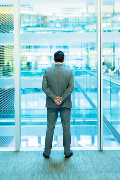 Businessman standing at atrium window with hands behind back