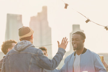 Young men high fiving at rooftop party