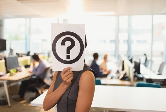 Portrait businesswoman holding question mark printout over her face in office