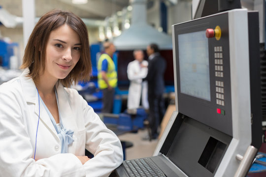 Portrait smiling female engineer at control panel in steel factory