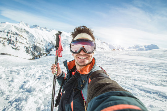 Skier man is taking a selfie on a snowy mountain at winter