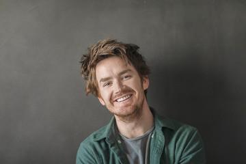 Closeup portrait of smiling handsome man against black background