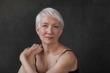 Closeup portrait of confident mature woman with short white hair against black background