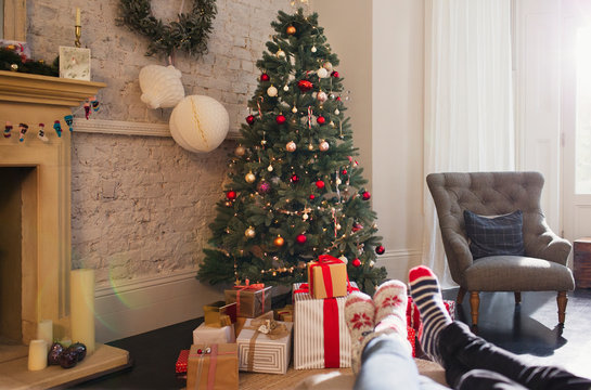Relaxed couple wearing socks feet up near Christmas tree in living room