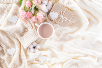 Pink paper hearts with gift box and roses, coffee cup on , beige sweater on cream colour knitted...