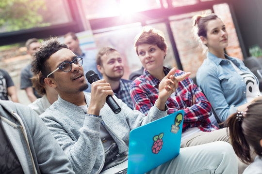 Man in audience laptop asking question microphone at conference