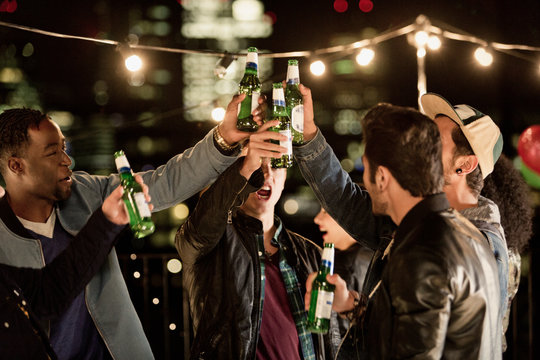 Young men toasting beer bottles at rooftop party
