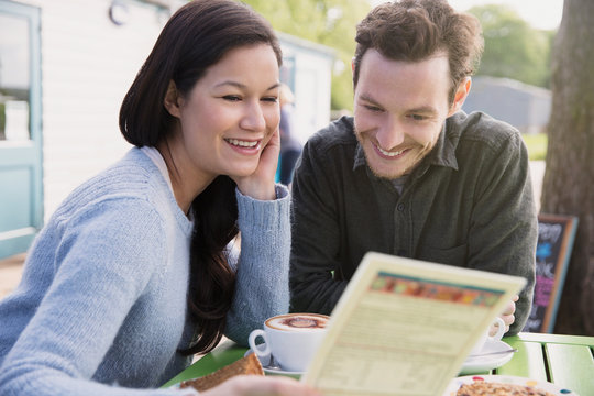 Smiling couple reading menu at outdoor cafe