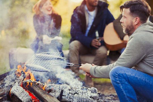 Man frying fish in grill basket over campfire near friends