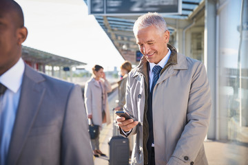 Businessman texting with cell phone outside airport