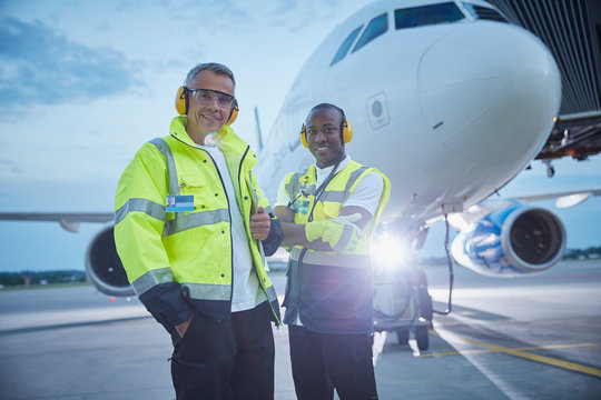 Portrait confident air traffic control ground crew workers near airplane on airport tarmac