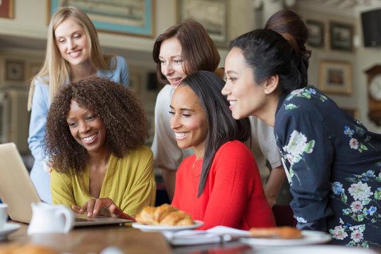 Women friends using laptop at restaurant table