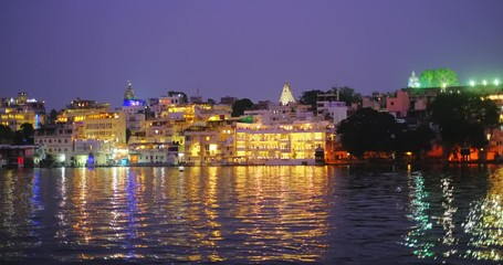 Wall Mural - Udaipur Lal ghat, houses and City Palace on bank of lake Pichola with water ripples - Rajput architecture of Mewar dynasty rulers of Rajasthan. Sunset at Udaipur, India. Horizontal panning