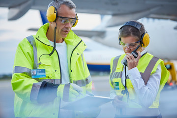Air traffic control ground crew workers clipboard talking on airport tarmac