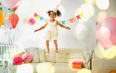 Playful girl jumping on sofa