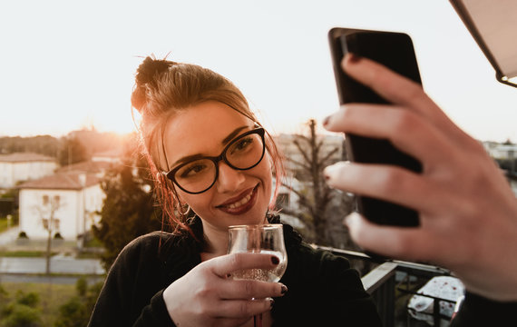 Portrait of a young smiling girl taking selfie drinking a glass of red wine during sunset on the roof of a house - Wide shoot of millenial woman using digital device to take picture of the joy moment