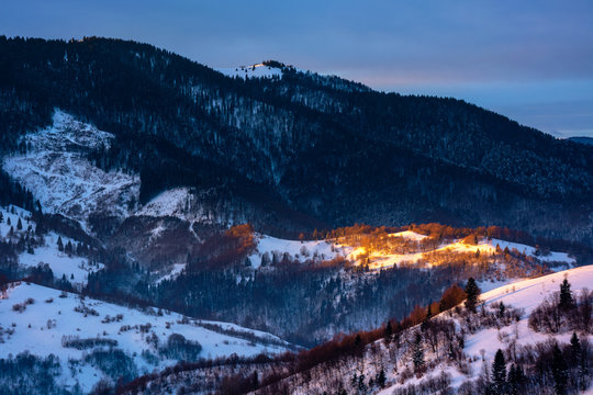winter countryside scenery at dawn. landscape with spot of first light on snow covered hill. dark coniferous distant forest in shade of the mountain. cold weather.