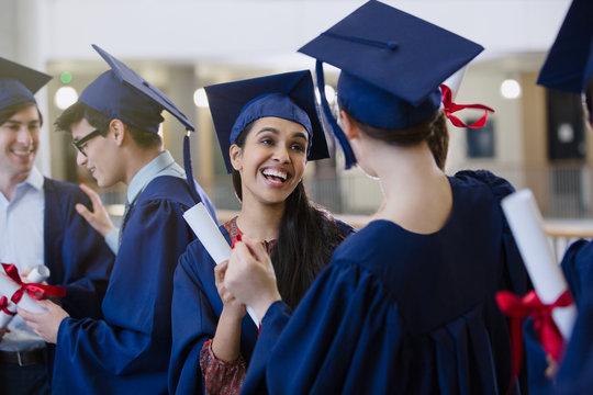 Happy female college student graduates cap gown diplomas celebrating
