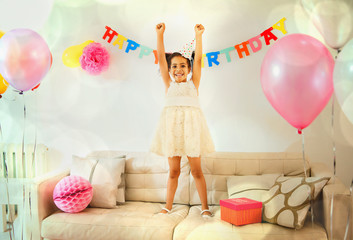 Portrait confident girl with arms raised on sofa at birthday party