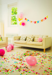 Birthday sign, balloons and confetti in living room
