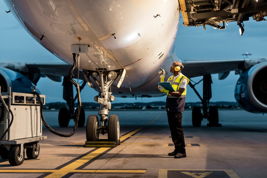 Airport ground crew worker checking airplane on tarmac