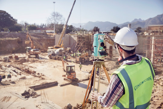 Construction worker surveyor using theodolite at sunny construction site