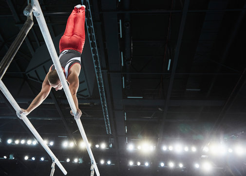 Male gymnast performing upside-down handston parallel bars in arena