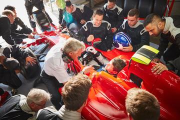 Manager and pit crew surrounding formula one driver in race car