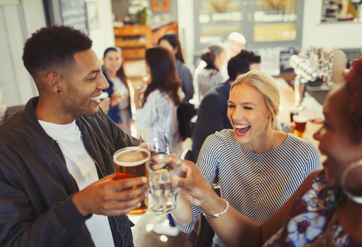 Laughing friends toasting beer and wine glasses at bar