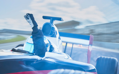 Formula one race car driver cheering, gesturing fist on sports track