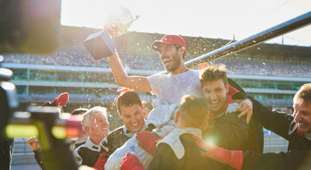 Formula one racing team carrying driver trophy on shoulders, celebrating victory