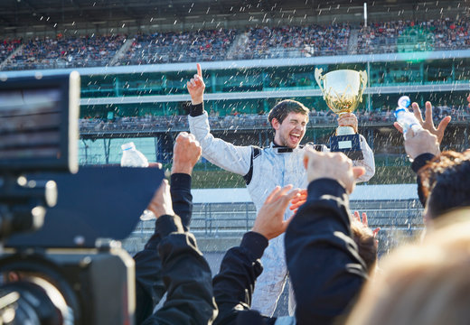 Formula one racing team spraying champagne on driver trophy, celebrating victory on sports track