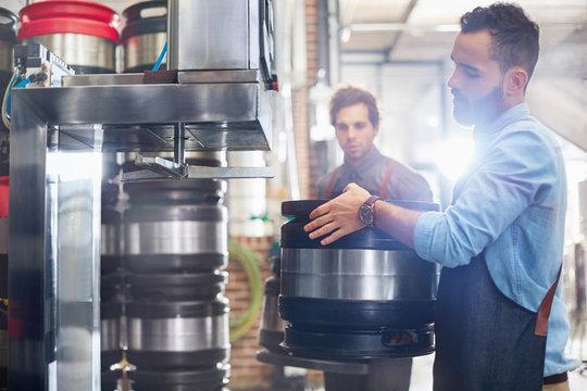 Male brewers filling kegs in brewery