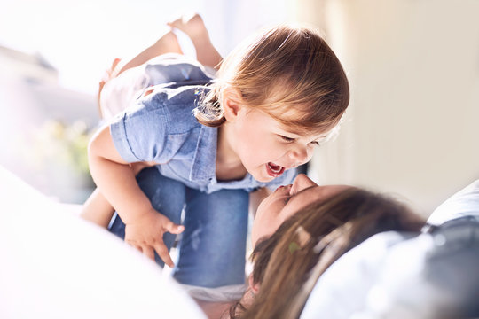 Playful mother holding laughing baby son on knees