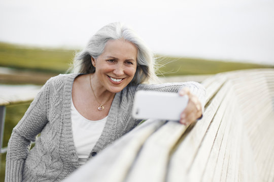 Smiling senior woman taking selfie at boardwalk ledge