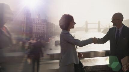 Silhouette business people handshaking on sunny bridge over River Thames, London, UK