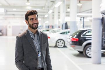 Portrait smiling car salesman looking away in car dealership auto repair shop