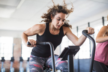 Determined young woman riding elliptical bike in gym