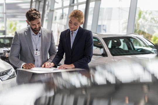 Car salesman watching female customer signing financial contract paperwork in car dealership showroom