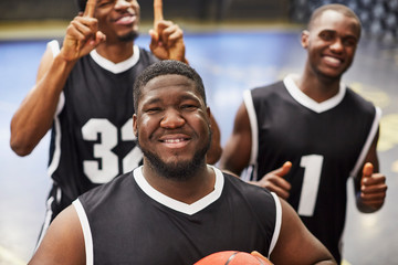 Portrait smiling, confident young male basketball player team in black jerseys gesturing, celebrating victory