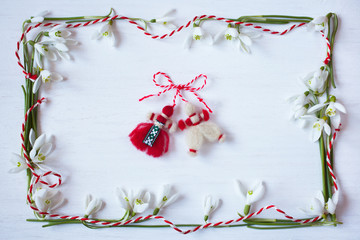 White wooden background with spring snowdrops and red and white martenitsa