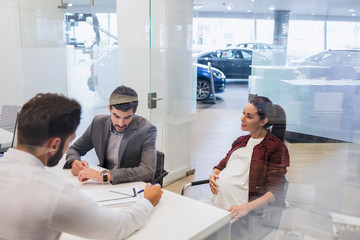 Car salesman explaining financial contract paperwork to pregnant couple customers in car dealership office
