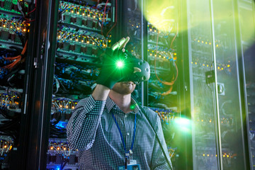 Male computer programmer using virtual reality simulator glasses glowing glove in server room