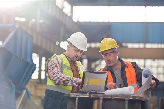 Male foreman and engineer working at laptop with blueprints in factory