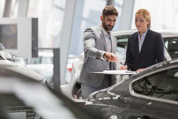 Car sales people meeting, examining new car in car dealership showroom