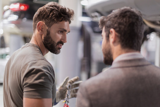Auto mechanic talking, explaining to customer in auto repair shop