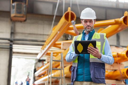 Serious male engineer using digital tablet in factory