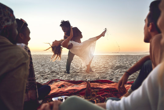 Playful young couple dancing on sunny summer beach